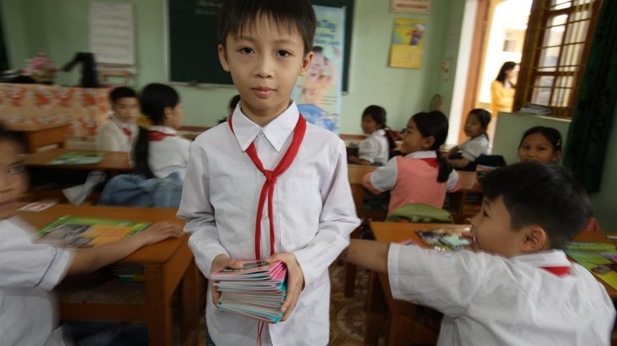 © UNICEF/UNI97996/Jim Holmes - Hieu is the class monitor and hands out some of the small books from the UNICEF supplied Hygiene Kit at Thi Son primary school (Kim Bang district) Ha Nam province, Viet Nam. Many children fear violence as a result of not doing as well as expected on school exams.