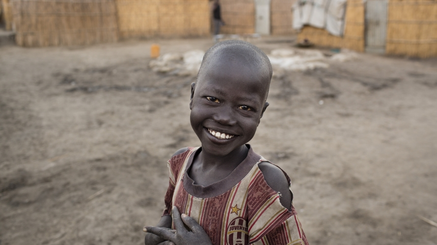 South Sudanese Gedain Galwak, 8, smiles as he waits in line for the water to be turned on in the morning, in the Protection of Civilians (PoC) site in Bentiu, South Sudan
