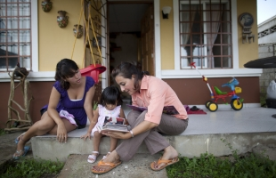 Nelly Salinas (Right) helps her 21-month-old foster daughter, Milagro Carolina Kastano, look at an album of photographs, outside their home in Panama City, the capital. © UNICEF/UNI134960/Dormino