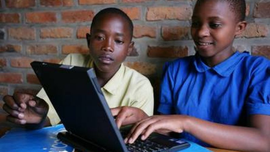 A girl and a boy use a laptop computer