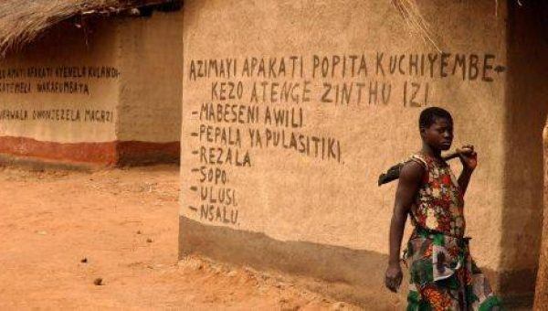 MDGs - woman walking in front of written walls