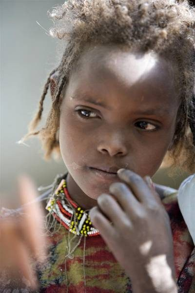 ©UNICEF/NYHQ2009-2267/Holt - A girl listens to a discussion at a community meeting regarding FGM/C and other practices in Kabele Village, in Amibara District, Afar Region. The meeting was organized by the Rohi-Weddu Pastoral Women Development Organization. UNICEF staff members are also in attendance.